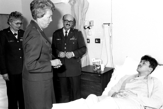 GEN Wells, chief nurse of the Air Force, talks to a patient during her visit to the 48th Tactical Fighter Wing Hospital. COL Reddman, hospital vice commander, and COL Halley, hospital chief nurse, stand behind GEN Wells