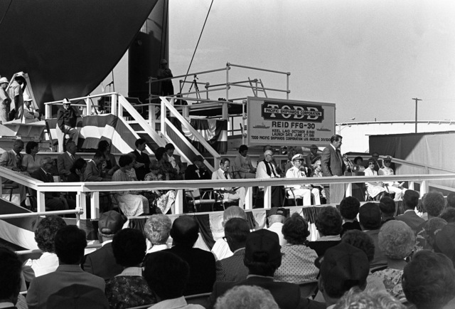 A overall view of guests and distinguished speakers attending christening and launching ceremonies for the guided missile frigate USS REID (FFG 30) at the Todd Pacific Shipyards Corp., Los Angeles Division
