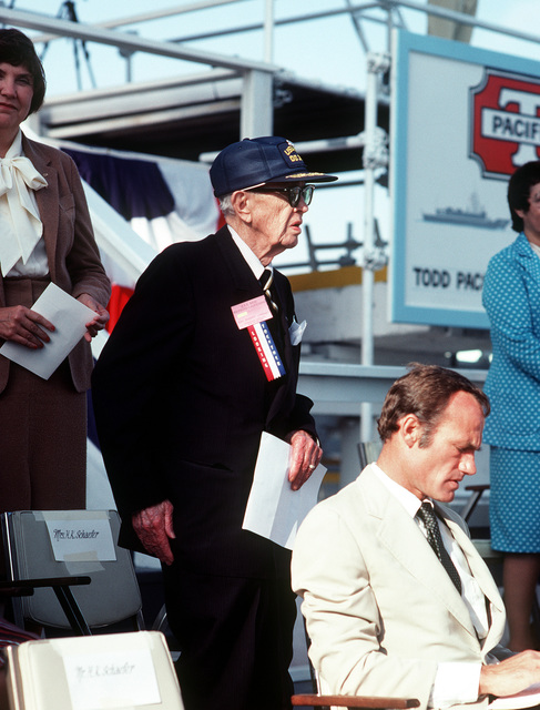 A view of Rep. Barry M. Goldwater Jr., R-Arizona, seated on the speakers platform during christening and launching ceremonies for the guided missile frigate USS REID (FFG-30). Standing behind him is retired ADM Robert B. Carney, former Chief at Naval Operations, at the Todd Pacific Shipyards Corp., Los Angeles Div