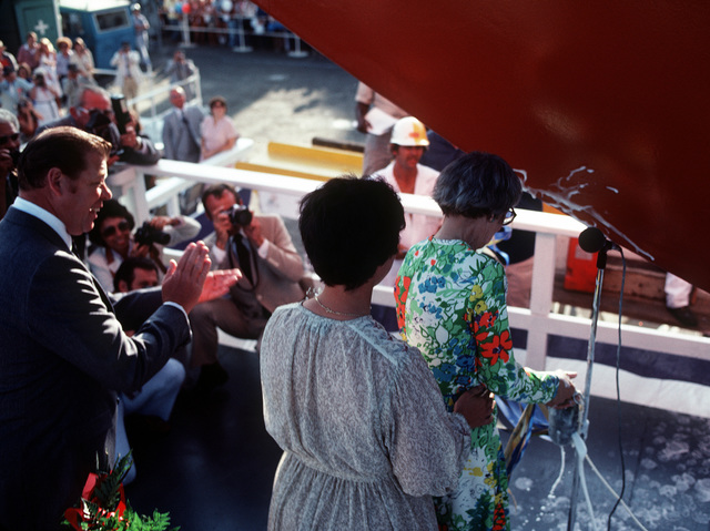 Sponsor Mrs. William C. Abhau (right) with her daughter Miss Elliot Abhau assisting, christens the USS REID (FFG-30) during launching ceremonies. Mrs. Abhau is the great-great granddaughter of Sailing Master Chester Reid for which this guided missile frigate is named at the Todd Pacific Shipyards Corp., Los Angeles Div