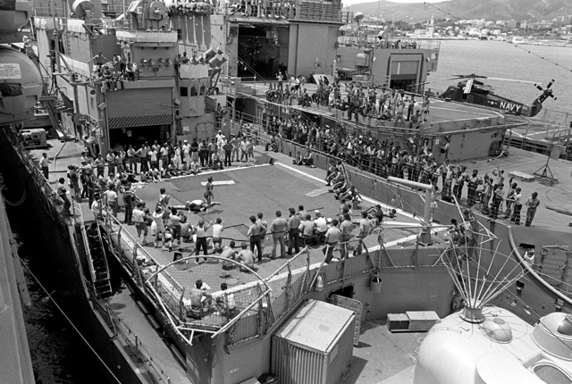 Crewmen watch from the decks of the guided missile cruiser USS WAINWRIGHT (CG-28) and the destroyer USS THORN (DD-988) as members from wrestling teams aboard each ship compete in an intra-ship tournament on the helicopter pad of the WAINWRIGHT. The tournament, which also includes the wrestling team from the frigate USS MILLER (FF-1091), is going on during 12-day upkeep period