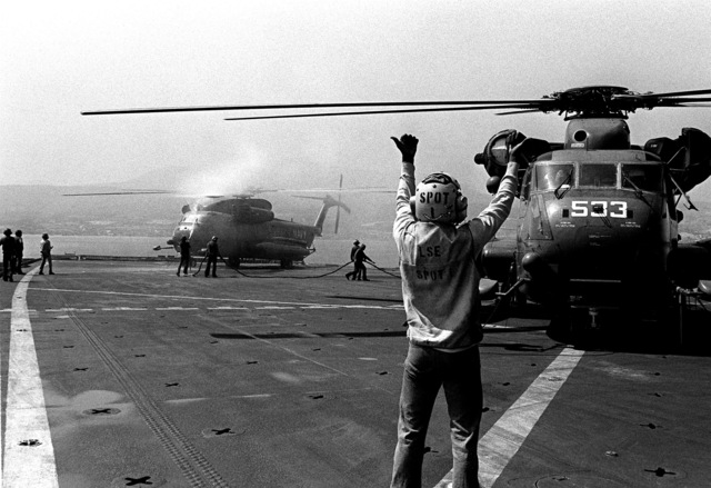 A flight deck crewman directs the pilot of a Helicopter Mine Countermeasures Squadron 14 (HM-14) RH-53D Sea Stallion helicopter just before takeoff from the deck of the amphibious transport dock USS NASHVILLE (LPD-13). The NASHVILLE and the helicopters aboard it are participating in Mine Countermeasures Task Group 1-81 (MCMTG 1-81) exercises to increase the mine countermeasures capabilities of the seven participating NATO countries