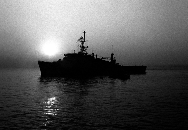 A silhouetted port beam view of the amphibious transport dock USS NASHVILLE (LPD-13) while anchored at night. During the day the NASHVILLE is the center of activity for exercises conducted by Mine Countermeasures Task Group 1-81 (MCMTG 1-81), which consists of navy units from seven NATO countries, and which was formed to increase their mine countermeasures capabilities