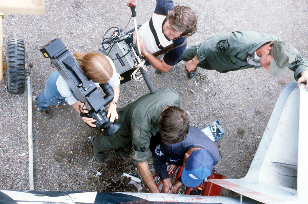 A view of team members from the 2952nd Combat Logistics Support Squadron during repair procedures on an F-101 Voodoo aircraft. A camera crew from the National Broadcasting Company (NBC) is filming the training exercise