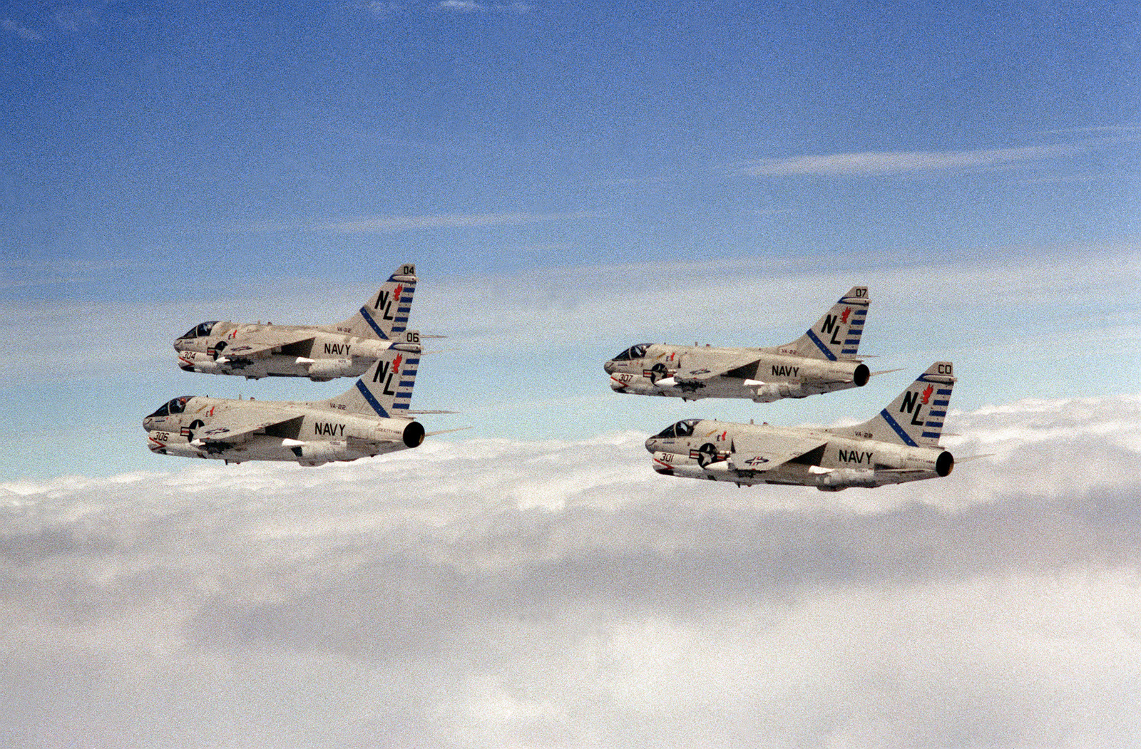 An air-to-air left rear view of four A-7 Corsair II aircraft from Attack Squadron 22 (VA-22). The Carrier Air Wing 15 (CVW-15) embarked aboard the aircraft carrier USS KITTY HAWK (CV-63)