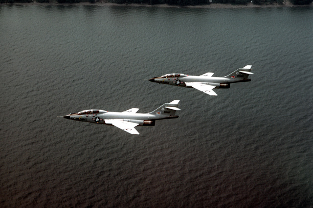 AN air-to-air left side view of two F-101 Voodoo aircraft near Niagara Falls during exercise Sentry Castle '81. The aircraft are assigned to the 107th Fighter Interceptor Group, 136th Fighter Interceptor Squadron, New York Air National Guard
