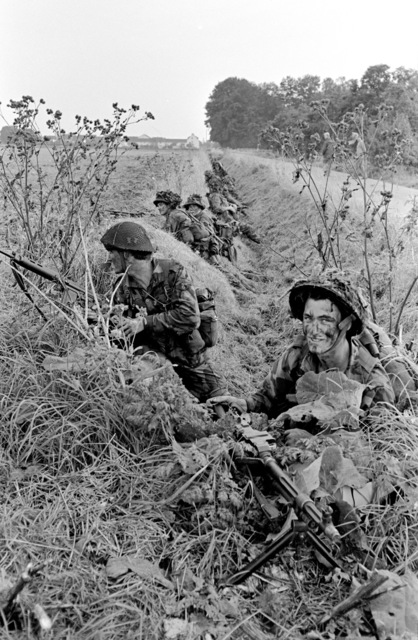 Members of the United States (US) Air Force 82nd Airborne Division line a farm land ditch after parachuting into the area during exercise REFORGER/AUTUMN FORGE 1980. AUTUMN FORGER is a reserve airdrop and associated ground movements taking place both here an in Germany and involving mostly US and British troops and equipment