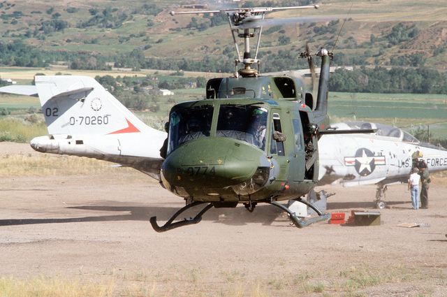 Personnel from the 2952nd Combat Logistics Support Squadron disembark a UH-1 Iroquois helicopter (foreground) to make repairs to an F-101 Voodoo aircraft (background), during a training exercise