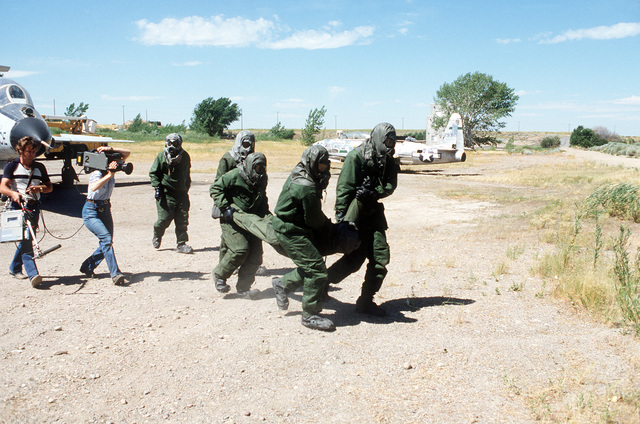 """Team members from the 2952nd Combat Logistics Support Squadron, wearing chemical protection suits, begin life saving procedures on a member who was overcome by """"nerve gas fumes"""", during repair procedures on an F-101 Voodoo aircraft. A camera crew from the National Broadcasting Company (NBC) is filming the training exercise"""