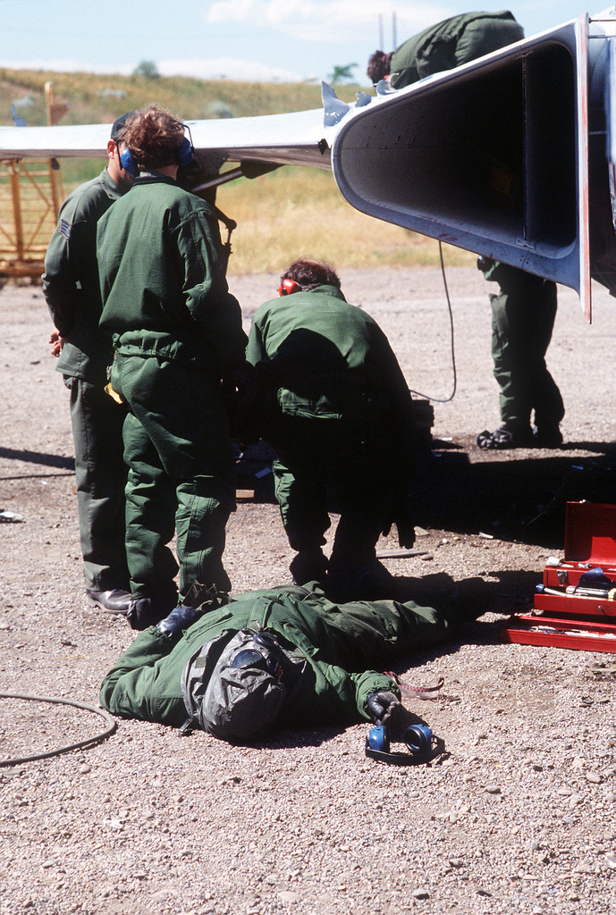 """Team members from the 2952nd Combat Logistics Support Squadron, wearing chemical protection suits, begin life saving procedures on a member who was overcome by """"nerve gas fumes"""", during repair procedures on an F-101 Voodoo aircraft"""