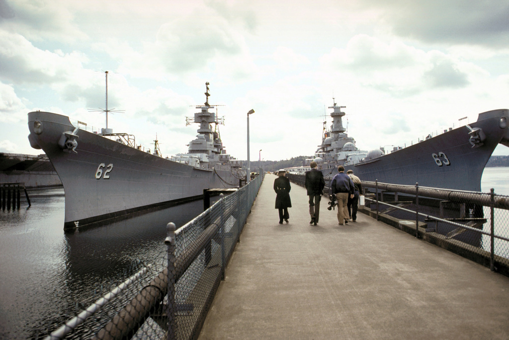 The two battleships NEW JERSEY (BB-62) and MISSOURI (BB-63) docked on either side of a Naval Inactive Ship Maintenance Facility pier