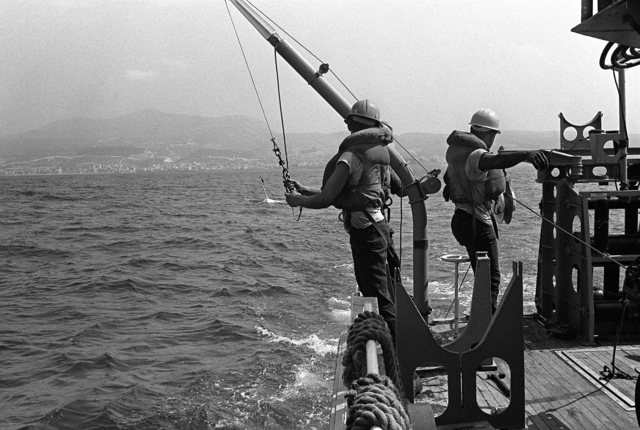 Two crewmen aboard minesweeping boat 51 (MSB-51) look toward the water just after dropping a float during exercises conducted by Mine Countermeasures Task Group 1-81 (MCMTG 1-81). The task group, consisting of navy units from seven NATO countries, was formed to increase their mine countermeasures capabilities