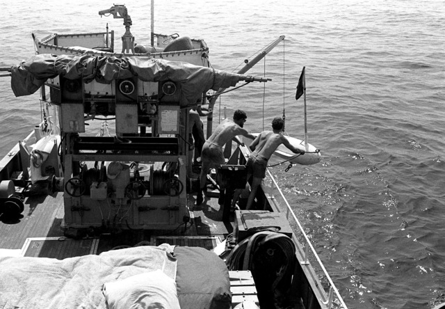 Two crewmen near the deck edge of minesweeping boat 51 (MSB-51) prepare to drop a float into the water during exercises conducted by Mine Countermeasures Task Group 1-81 (MCMTG 1-81). The task group, consisting of navy units from seven NATO countries, was formed to increase their mine countermeasures capabilities