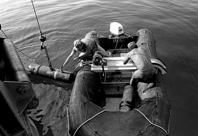 Two members from Explosive Ordnance Disposal Team Two, Detachment 40 (EOD-2, Det 40) work from an inflatable raft while participating in exercise conducted by Mine Countermeasures Task Group 1-81 (MCMTG 1-81). The task group, consisting of navy units from seven NATO countries, was formed to increase their mine countermeasures capabilities