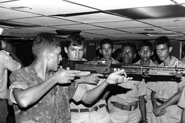 While aboard the dock landing ship, USS PLYMOUTH ROCK (LSD-29), LCPL William Robb of Weapons Co., 3rd Bn., 6th Mar., shows a group of Colombian Marines how to hold an M-60A1 machine gun in the off-hand position. The Marines are preparing for the joint amphibious landing exercise, Unitas XXII