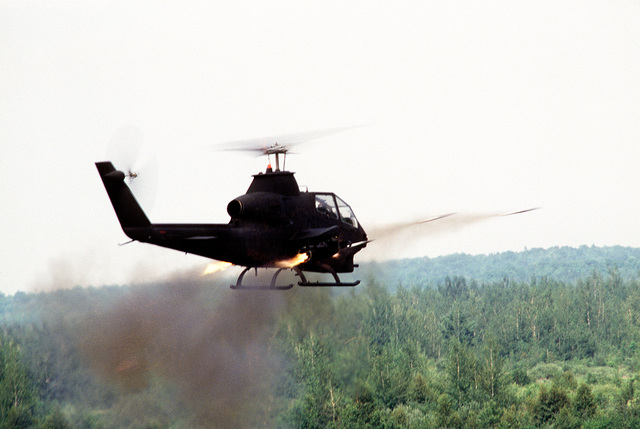 A right rear view of an AH-1 Cobra helicopter launching missiles for a demonstration during exercise Sentry Castle '81. The helicopter is from the Army Air National Guard