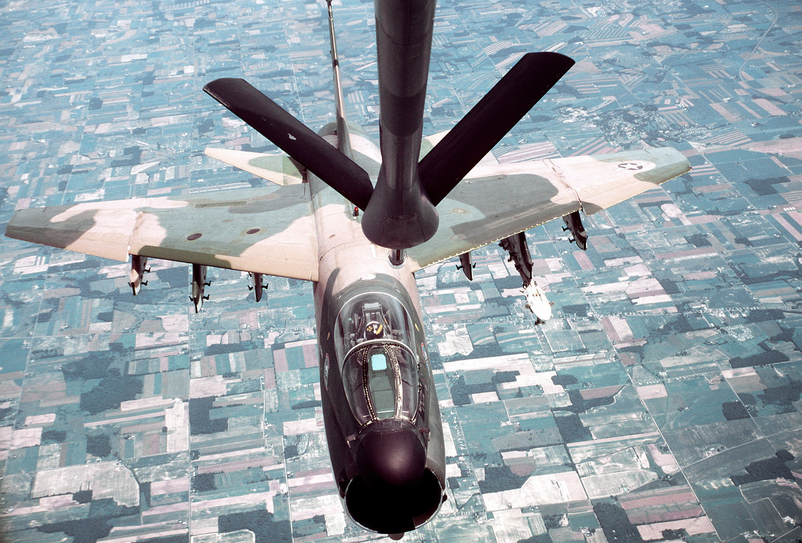 AN air-to-air front view of an A-7 Corsair II aircraft heading toward a KC-135 Stratotanker aircraft for refueling, as seen from the boom operator's section of the tanker, during exercise Sentry Castle '81. The Corsair is from the 112th Tactical Fighter Group, Pennsylvania Air National Guard, and the Stratotanker is from the 147th Air Refueling Squadron