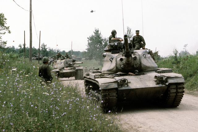 A convoy of an M-60 aggressor forces tank group maneuvers through a field. The soldiers are assigned to the Army Air National Guard, involved in exercise Sentry Castle '81