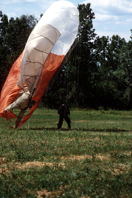 A pararescueman lands on the ground after jumping from a C-130 Hercules aircraft during exercise Sentry Castle '81. The airman is assigned to the 106th Aerospace Rescue and Recovery Squadron