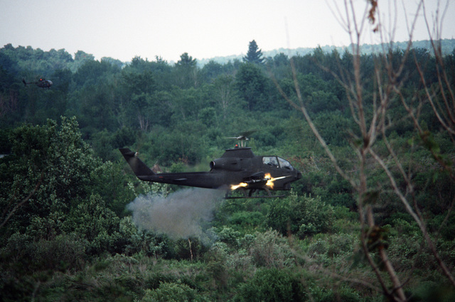 A right side view of an AH-1 Cobra helicopter launching missiles for a demonstration during Exercise Sentry Castle '81. The helicopter is from the Army Air National Guard