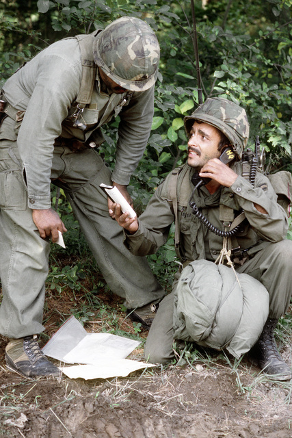 A soldier, using a combat radio directory, contacts coordinates on radio during field training. The soldier and his teammate are assigned to the Army Air National Guard, involved in exercise Sentry Castle '81