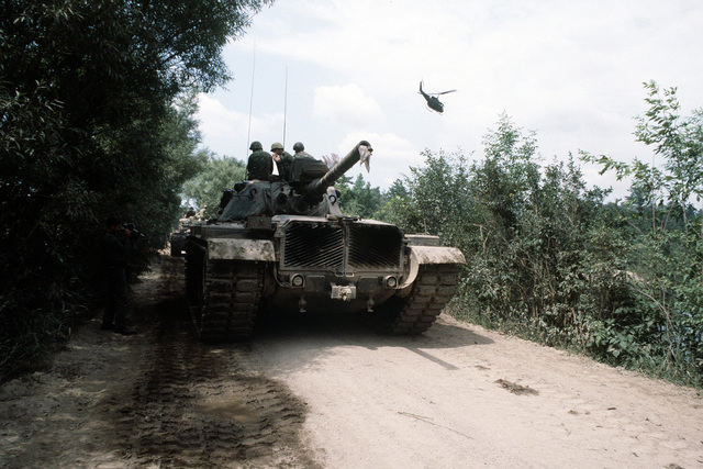 An Air Force motion picture photographer documents a convoy of M-60 tank aggressors involved in exercise Sentry Castle '81