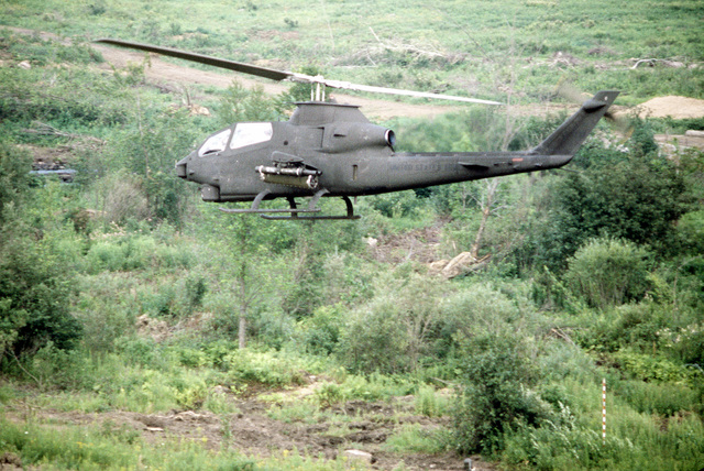AN air-to-air left side view of an AH-1 Cobra helicopter, armed with a missile launcher, participating in exercise Sentry Castle '81. The helicopter is from the Army Air National Guard