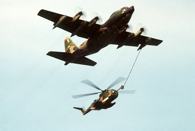 AN air-to-air right front view of an HC-130P Hercules aircraft refueling a CH-3 Jolly Green Giant helicopter during exercise Sentry Castle '81. Both aircraft are from the New York Air National Guard