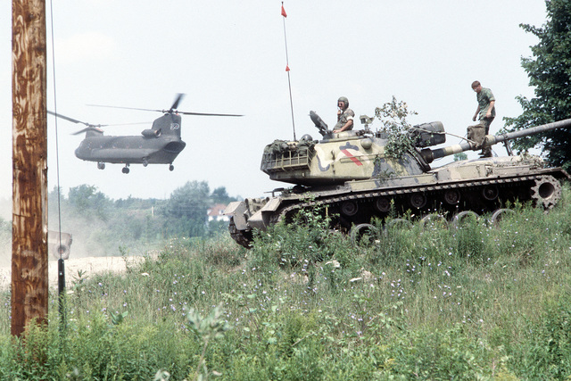 AN M-60 aggressor forces tank group is in convoy moving through a field as an Army CH-47 Chinook helicopter (background) nears the ground. The soldiers are assigned to the Army Air National Guard, involved in exercise Sentry Castle '81