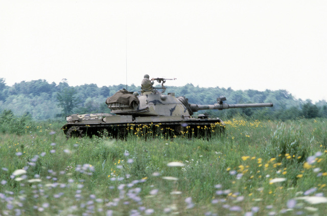 AN M-60 aggressor forces tank group maneuvers through the field during training. The soldiers are assigned to the Army Air National Guard, involved in exercise Sentry Castle '81