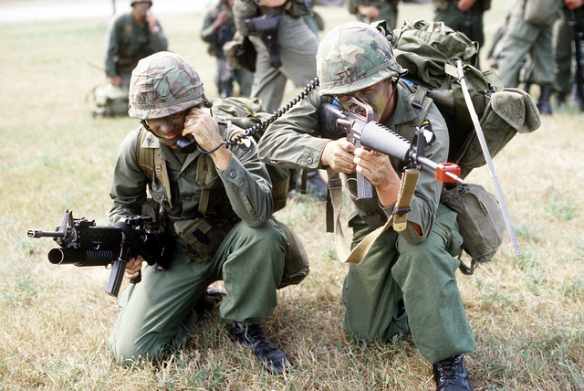 SGT Gary Carter, armed with an M-203 grenade launcher-equipped M-16 rifle, contacts a remote area by radio as PVT Clarence mans an M-16 rifle in field practice during exercise Sentry Castle '81. Both troopers are assigned to the Army 101st Battalion, 503rd Infantry Division