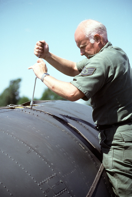 SSGT Floyd H. Godfrey unscrews an A-10 Thunderbolt II aircraft engine cowling panel for maintenance during exercise Sentry Castle '81. The airman is a machine shop scheduler for Carrier Air Conditioner Company five days a week and a guardsman on weekends