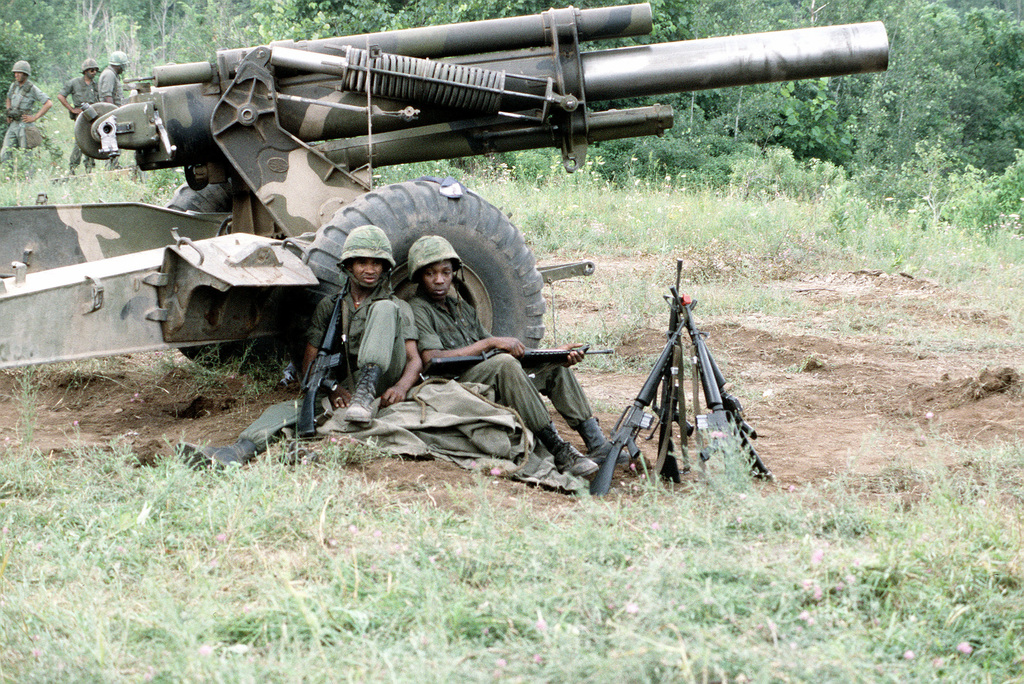 Two Army soldiers lean against an M-114 155mm towed howitzer after field training, part of exercise Sentry Castle '81. The soldiers are assigned to the Army Air National Guard