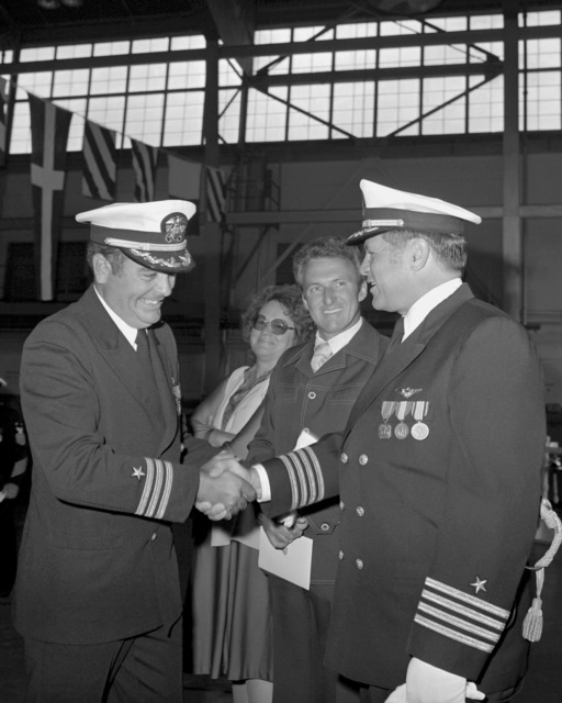 CAPT John M. McNabb, right, and CDR Rodney L. Franz shake hands as two distinguished guests look on following the change of command ceremony in which Franz is relieving McNabb as commanding officer of Attack Squadron 128 (VA-128)
