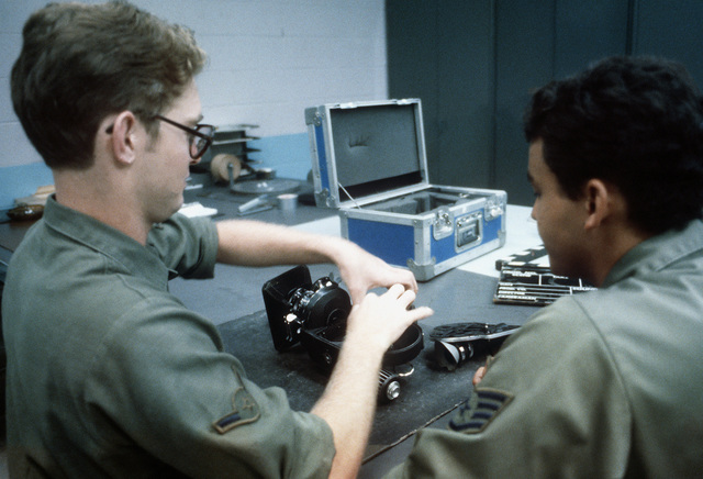 AMN Brant R. McCarthy receives training from SSGT John W. Rodrigues on the 16mm movie camera, during a mission briefing for the 1361st Audio Visual Squadron, Detachment Seven