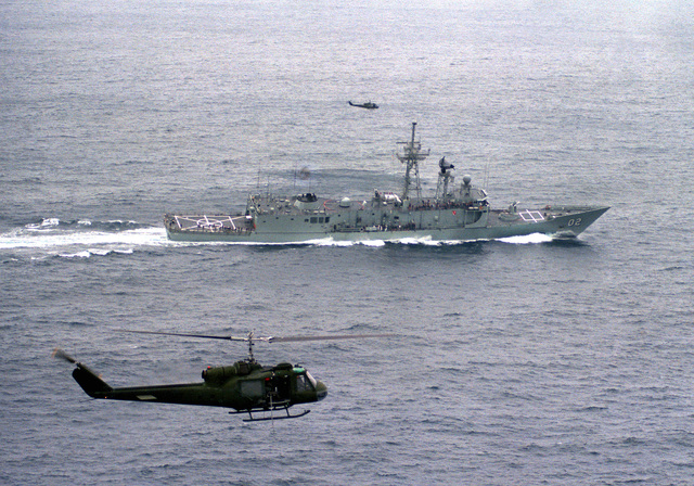 Aerial starboard beam view of the Australian Frigate HMAS CANBERRA (F-02) during its first Harpoon missile launch near the Pacific Missile Test Center, Point Mugu, California. Two UH-1 Iroquois helicopters, provide aerial coverage of the launching