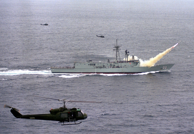 Aerial starboard beam view of the Australian Frigate HMAS CANBERRA (F-02) launching its first Harpoon missile near the Pacific Missile Test Center, Point Mugu, California. Three UH-1 Iroquois helicopters provide aerial coverage of the launching