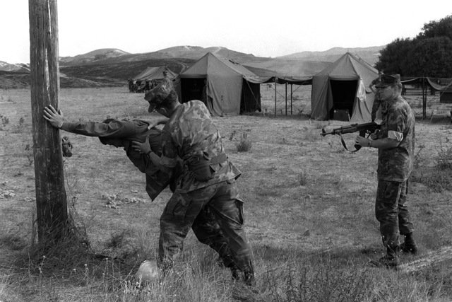 During a field combat training exercise at the Las Pulgas Lake area, an enemy aggressor is captured and is hastily interrogated by GYSGTs Robert Werkele and Tom Burke. The aggressor is SSGT Stephen Campbell. These Marines are reservists from International Telephone and Telegram Company (ITT)