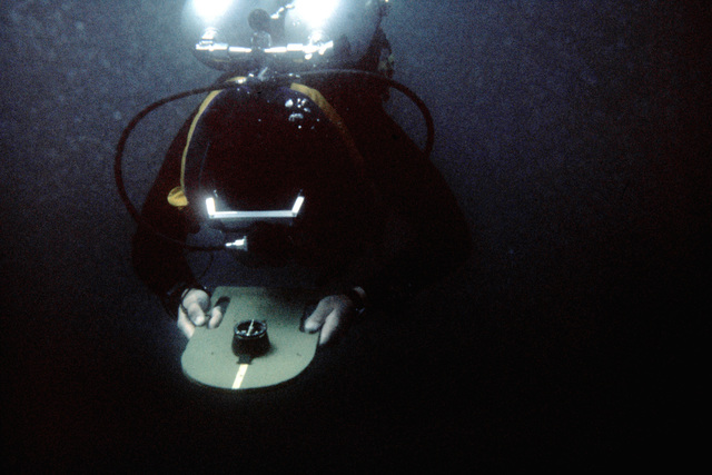 A combat control team member uses a wet compass while scuba diving during a water training exercise. The team member is from the 63rd Military Airlift Wing