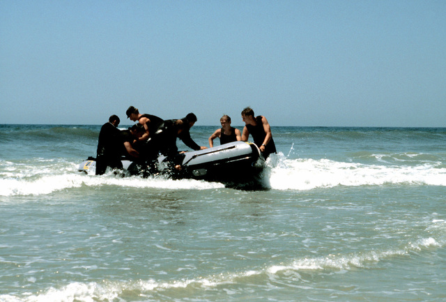 Combat control team members land ashore in an inflatable boat after a parachute drop during a water training exercise. The controllers are members of the 63rd Military Airlift Wing