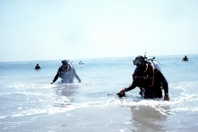 Combat control team scuba divers come ashore during a water training exercise. The airmen are from the 63rd Military Airlift Wing
