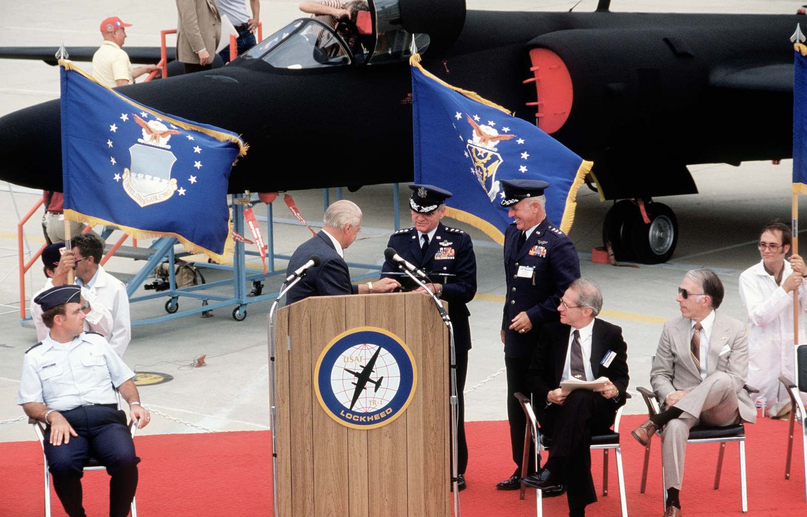 Kelly Johnson, developer of the original U-2 reconnaissance aircraft presents models of its successor, the new TR-1 aircraft (background) to LGEN James P. Mullins and LGEN John G. Albert during its rollout ceremony. LGEN Mullins is the new commander of the Air Force Acquisition Logistics Command and LGEN Albert is the former commander