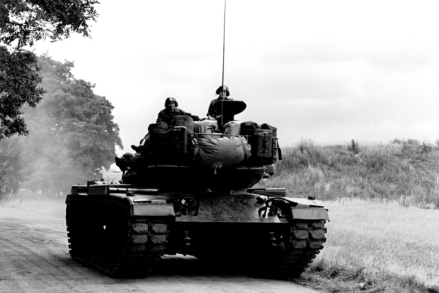 SPEC. 4 Raoul Menienta and 2LT Jim Iken, 7350th Air Base Group, take orientation training on a U.S. Army tank at Tempelhof Central Airport