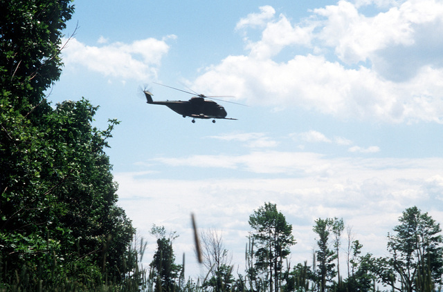 """An HH-3 Pelican helicopter from the 106th Aerospace Rescue and Recovery Group flies over prior to picking up a """"survivor"""" during Sentry Castle '81, a search and rescue exercise"""
