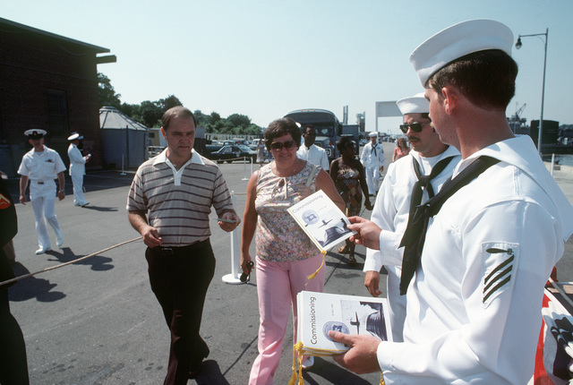 A crew member distributes programs to guests arriving for the commissioning of the nuclear-powered attack submarine USS DALLAS (SSN 700)