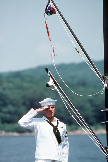A crewman salutes during the commissioning of the nuclear-powered attack submarine USS DALLAS (SSN 700). The commissioning pennant is flying from the mast