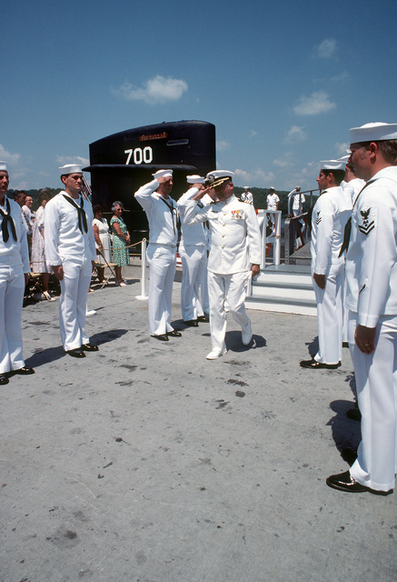 Chaplain (CDR) R.C. Mellett exchanges salutes with side boys at the conclusion of the commissioning of the nuclear-powered attack submarine USS DALLAS (SSN 700)