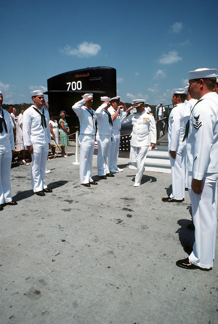 Chaplain (CMDR.) R.C. Mellett exchanges salutes with side boys at the conclusion of the commissioning of the nuclear-powered attack submarine USS DALLAS (SSN-700)