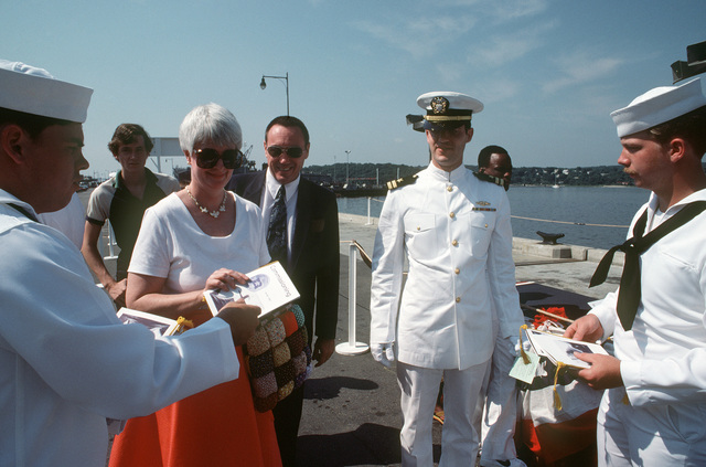 Crew members distribute programs to guests arriving for the commissioning of the nuclear-powered attack submarine USS DALLAS (SSN 700)