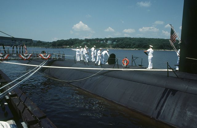 Crew members man their stations during the commissioning of the nuclear-powered attack submarine USS DALLAS (SSN 700)